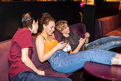 Happy multi-ethnic teenage friends relaxing on sofa while using smart phone at bowling alley - p426m1588395 by Maskot
