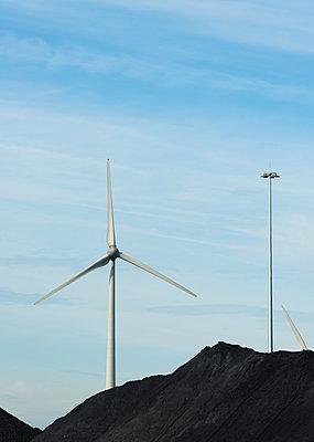 Wind turbines in between piles of coal in Flushing harbour, Netherlands - p429m1179641 by Mischa Keijser