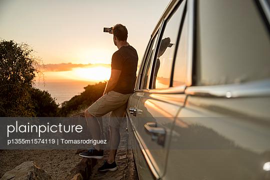 Mann fotografiert den Sonnenuntergang - p1355m1574119 von Tomasrodriguez