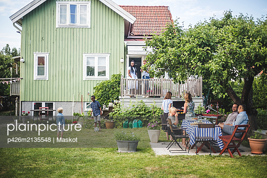 Mature friends having garden party while children playing in backyard during summer weekend - p426m2135548 by Maskot