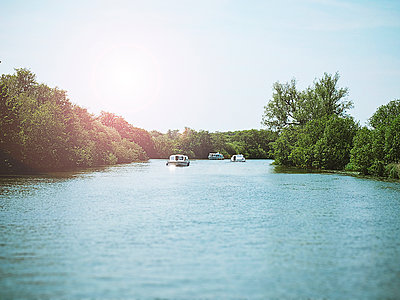 Pleasure boats on wide river, Norfolk, England - p1072m2167989 by Neville Mountford-Hoare