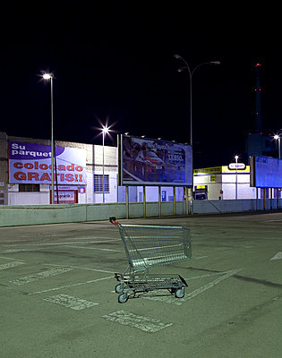 Shopping trolley abandoned in a car park outside a shopping mall at night in Barcelona (II) - p1072m829074 by Joan Seculi