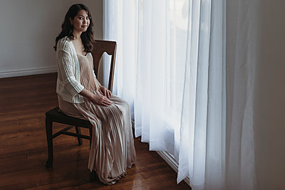 Full length portrait of mother sitting by window in studio - p1166m2131011 by Cavan Images