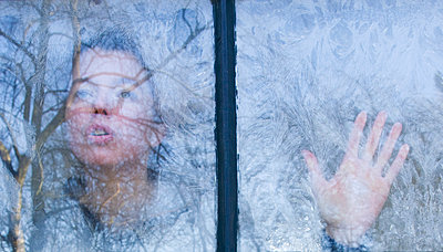 Woman looking through the windows which are covered with frost flowers - p1231m1043094 by Iris Loonen