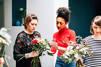 Florist students arranging bouquets at flower arranging workshop - p429m1418066 by Alys Tomlinson