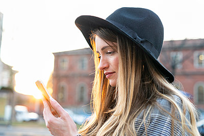 Stylish young woman with long blond hair looking at smartphone on city street - p429m2097879 by Francesco Buttitta