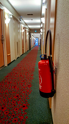 Extinguisher in the hallway of a hotel - p813m1154695 by B.Jaubert