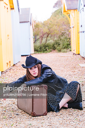 Woman with brown hair, long dress, cowboy hat, holding a suitcase - p1628m2195756 by Lorraine Fitch