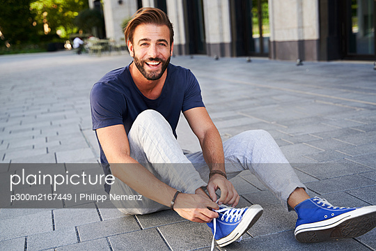 Portrait of happy man sitting on the ground in the city lacing his shoes - p300m2167449 by Philipp Nemenz