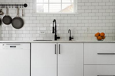 Kitchen sink and white subway tile backsplash - p1166m2073647 by Cavan Images