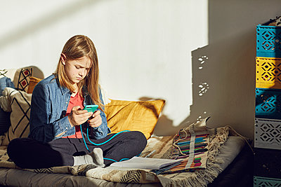 Girl sitting on bed at home doing homework and using smartphone - p300m2188908 by Maya Claussen