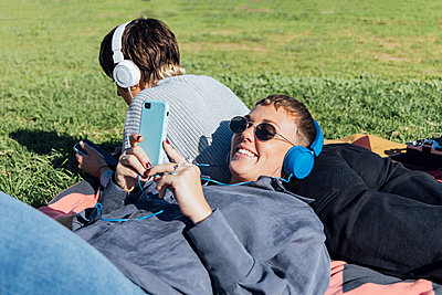 two women chilling and listening music on headphone in the riverside, Seville, Spain - p300m2253011 von Julio Rodriguez
