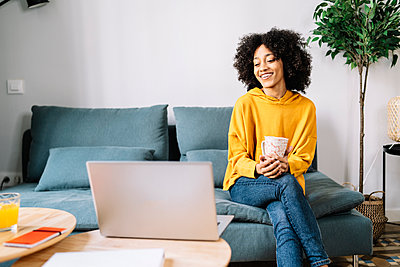 Smiling woman with mug looking at laptop while sitting at home - p300m2275352 by COROIMAGE