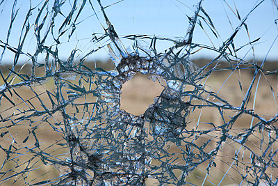 A broken glass window with hole in it - p301m799867f by Oliver Steinberger