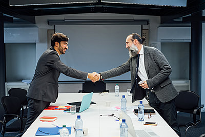 Business partners shaking hands at meeting in office - p429m2098054 by Eugenio Marongiu