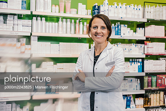 Confident pharmacist with arms crossed in chemist shop - p300m2243825 by Mareen Fischinger