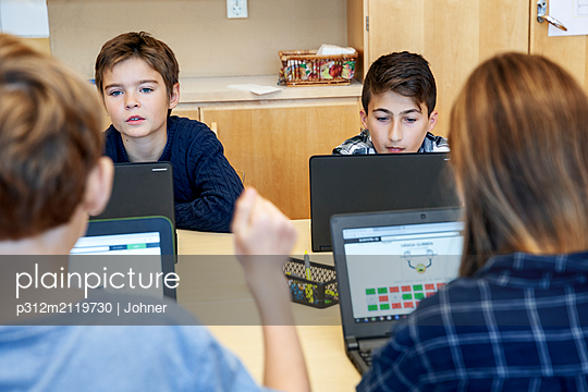Boys using laptops at school - p312m2119730 by Johner