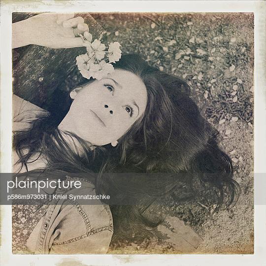 Junge Frau hält verträumt eine Blume in einer Hand - p586m973031 von Kniel Synnatzschke