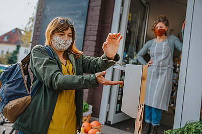Customer disinfecting her hands in front of organic food store, Cologne, NRW, Germany - p300m2256167 von Mareen Fischinger