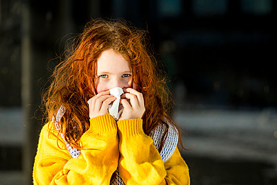 Girl with gray eyes cleaning nose outdoors - p300m2266335 by Irina Heß