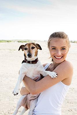 Junge Frau mit Hund am Strand - p341m1480688 von Mikesch