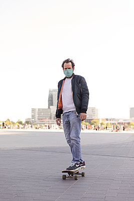Man with community mask on skateboard, social distancing due to Covid-19 - p788m2184016 by Lisa Krechting
