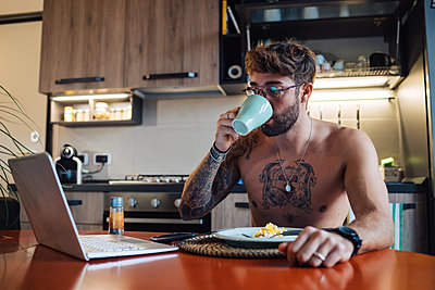 Mid adult man with tattoos drinking coffee while looking at laptop - p924m2097282 by Eugenio Marongiu