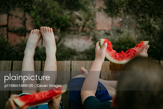 Overhead view of brothers eating watermelon while sitting at porch - p1166m1489120 by Cavan Images