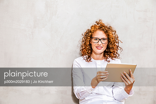 Portrait of redheaded young woman with tablet - p300m2029183 by Jo Kirchherr