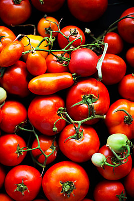 Red tomatoes on black background - p1166m2093962 by Cavan Images