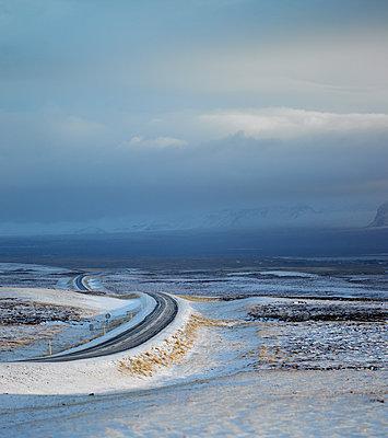 Rural road through snowy terrain in Iceland - p1166m2179673 by Cavan Images