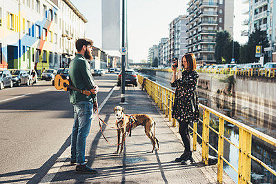 Young woman photographing boyfriend and dog by canal using instant camera - p429m1494246 by Eugenio Marongiu