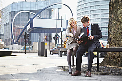 Two businesspeople sitting on railing in city - p429m803578f by Liam Norris