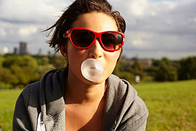 Teenage girl in sunglasses, blowing bubble gum - p924m734593f by Sverre Haugland