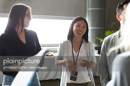 Happy businesswoman talking, networking at conference - p1192m2123216 by Hero Images