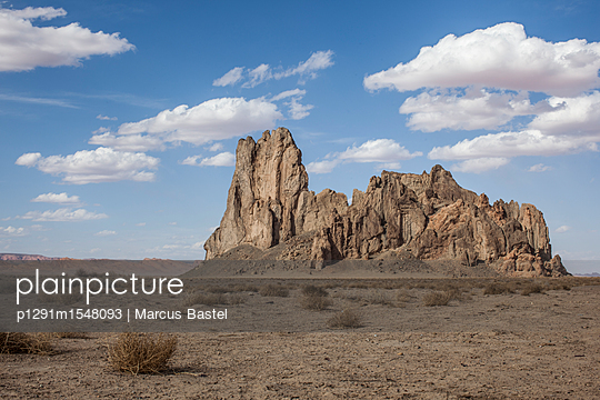 Large Freestanding Rock In A Desert Environment With Fluffy Clouds In Blue Sky - p1291m1548093 by Marcus Bastel