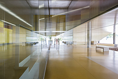 Business people handshaking in distance in modern office lobby corridor - p1023m1519853 by Martin Barraud