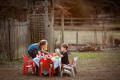 Side view of brother and sister having food at dining table in yard - p1166m1150439 by Cavan Images