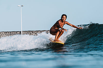 Full length action of female surfer on yellow surfboard - p1166m2130031 by Cavan Images
