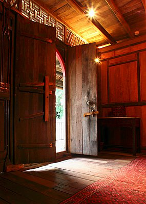 Traditional foyer with half-open front door in Oriental wooden house - p1183m996987 by Morris, Steven