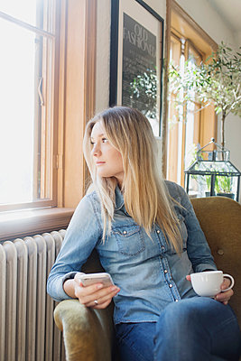 Thoughtful woman with mobile phone and coffee cup looking out through cafe window - p1185m1027534f by Astrakan