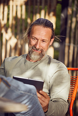 Close-up of bearded man reading book while relaxing on chair in yard - p300m2214037 by Maya Claussen