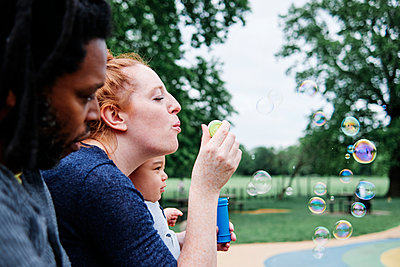 Woman blowing bubbles with family at park - p300m2287390 by Angel Santana Garcia