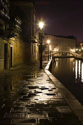 Italy, Venice, sidewalk along canal illuminated by street lamps at night - p6751347 by Sandro Di Carlo Darsa