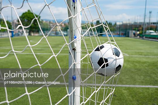 Soccer ball hitting net against sky