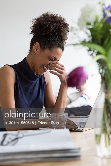 Hübsche Frau mit Afro sitzt lachend an ihrem Arbeitsplatz  - p1301m1589618 von Delia Baum