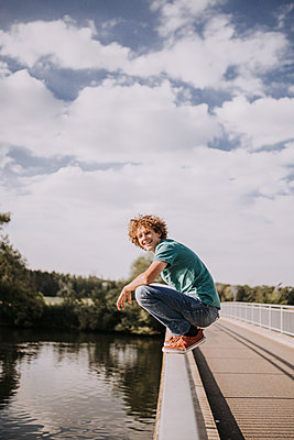 Young man on bridge railing, portrait - p1267m2259691 by Jörg Meier
