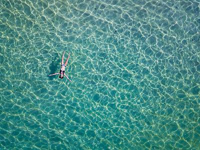 Indonesia, Bali, Melasti, Aerial view of Karma Kandara beach, woman floating on water - p300m2042548 by Konstantin Trubavin
