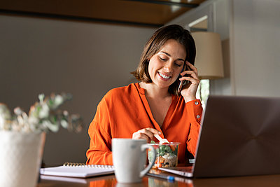 Smiling businesswoman talking on smart phone while eating salad at home - p300m2206519 by VITTA GALLERY