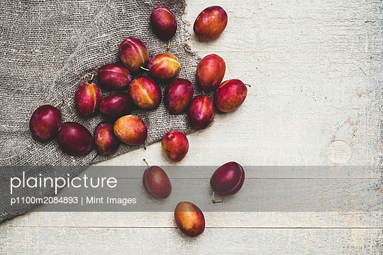 High angle close up of fresh damsons on grey cloth. - p1100m2084893 by Mint Images